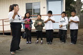 Children of migrants, many of them from indigenous Mixtec families from Oaxaca, at Ohlone Elementary School. Casimira Salazar, a Migrant Education Instructor, leads pupils in a song honouring the firs... - David Bacon - 19-11-2010
