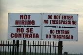 California: With a recession and a surplus of unemployed workers, many dairies are not hiring. A sign outside a dairy in Central Valley. Not Hiring and Do not enter, no trespassing in English and Span... - David Bacon - 2010,2010s,agricultural,agriculture,America,American,americans,BAME,BAMEs,bilingual,BME,bmes,capitalism,capitalist,casual workers,cattle,communicating,communication,cow,cows,CRLA,dairies,dairy,Dairy h