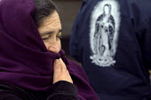 An elderly woman with Our Lady of Guadalupe, the Mexican Icon. Families of Mexican farmworkers receive bags of food at the San Benito County Community Food Bank. Their pay is so low they sometimes can... - David Bacon - 04-06-2011