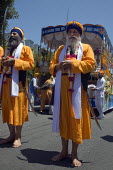 Religious devotees hold swords as they walk. Sikhs parade through the streets of Berkeley California on the anniversary of the death of GuruArjan Dev Ji, which is celebrated as a day of peace. - David Bacon - 12-06-2011