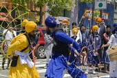 During the parade dancers spin webs of ropes and balls. Sikhs parade through the streets of Berkeley California on the anniversary of the death of Guru Arjan Dev Ji, which is celebrated as a day of pe... - David Bacon - American,2010s,2011,ACE,America,American,americans,anniversary,Arjan,Asian,asians,BAME,BAMEs,Black,BME,bmes,California,culture,dance,dancer,dancers,dancing,death,DEATHS,Dev,Diaspora,died,diversity,eth