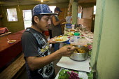 Families live in the Royce Bone labor camp in Nash County. These migrant families come from Mexico, mostly Veracruz, and work in the fields of tobacco and sweet potatoes. Workers get dinner in the cam... - David Bacon - 04-08-2011