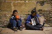 Two Oaxacan children beg on the street in Oaxaca just before Christmas, a girl playing accordion and a boy with a begging bowl. Oaxaca, Mexico - David Bacon - 17-12-2011