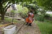 Vanessa Huang, a poet, activist and cellist, performs playing cello and singing, practicing in her garden, Oakland, California - David Bacon - 04-06-2012