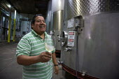 A technician in the laboratory of the Martin Ray Winery, Santa Rosa, California, tasting a glass of white wine. He came to the U.S. as a migrant farmworker and speaks Triqui, spoken by indigenous peop... - David Bacon - American,2010s,2012,agricultural,agriculture,America,American,americans,Amerindian,Amerindians,California,capitalism,capitalist,Diaspora,EBF,Economic,Economy,EMOTION,EMOTIONAL,EMOTIONS,employee,employ