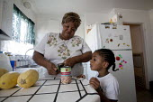 Oakland, California: Opening a can of beans. Grandmother looking after her grandson Tayvion at home with groceries from a food bank in Alameda County. Often her family doesn't have enough money to buy... - David Bacon - 01-11-2013