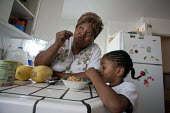 Oakland, California: Grandmother looking after her grandson Tayvion at home with groceries from a food bank in Alameda County. Often her family doesn't have enough money to buy food and pay rent, and... - David Bacon - 01-11-2013