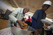 Oakland California- Elderly at a Community Food Bank. Pensioners eat lunch at St. Mary's Center in Oakland which provides food programs for poor people. - David Bacon - American,2010s,2013,adult,adults,African American,African Americans,age,ageing population,America,American,americans,BAME,BAMEs,black,BME,bmes,BREAK,Catholic,center,Church,churches,communities,communi