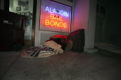 California: A homeless man sleeping on the sidewalk, sheltering in the doorway below a neon sign advertising a Bail Bonds agent. - David Bacon - American,2010s,2014,advertising,African American,America,American,americans,asleep,at,bag,bags,bench,black,blanket,BLANKETS,cities,city,CLJ,cold,communicating,communication,doorway,EQUALITY,excluded,e