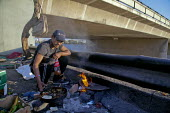 Tijuana, Mexico - Homeless people have set up a camp in the riverbed of the Tijuana River, in downtown Tijuana, not far from the U.S. Mexico border. Juan Guerra, a Zapotec migrant from Oaxaca, cooks a... - David Bacon - 09-09-2014