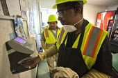 California- Workers at the recycling sorting facility of Alameda County Industries clock on at the start of their shift with a hand scanner Biometric Handscanner clocking in machine - David Bacon - 18-02-2015