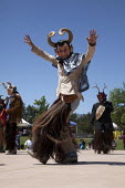 California, Danza de los Diablos, or the Dance of the Devils. Dancers from the Triquis of Oaxaca, now living as migrants in the USA, at a festival of Oaxacan indigenous culture in Greenfield, where ma... - David Bacon - 2010s,2015,ACE,America,American,americans,Amerindian,Amerindians,arts,California,costume,costumes,culture,dance,dancer,dancers,dancing,Devils,Diaspora,festival,FESTIVALS,fiesta,folk dance,foreign,fore