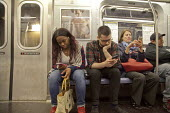 Passengers on a New York City subway train. USA - David Bacon - American,2010s,2015,adult,adults,advertisement,advertisements,advertising,African American,African Americans,America,American,americans,BAME,BAMEs,black,BME,bmes,call,calls,carriage,carriages,CELLULAR