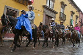 Mexico, Fiesta for St. Michael, the patron saint of San Miguel de Allende. Cowboys parade through the streets on their horses. The horses are then blessed by a priest in front of the church on the mai... - David Bacon - &,2010s,2014,ACE,Allende,americas,Amerindian,Amerindians,animal,animals,Archangel,belief,blessing,Catholic,catholicism,Catholics,christian,christianity,christians,church,churches,conviction,cowboy,cow
