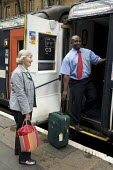 National Express East Coast main line staff, working at Kings Cross Station, London - Duncan Phillips - 2000s,2008,adult,adults,age,ageing population,assist,assisting,bag,bags,BAME,BAMEs,Black,BME,bmes,boarding,carriage,carriages,cities,city,coast,coastal,coasts,commute,commuter,COMMUTERS,COMMUTING,cros