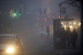 Shoppers waiting for the bus in heavy Fog, London. - Duncan Phillips - 2000s,2006,adult,adults,AUTO,AUTOMOBILE,AUTOMOBILES,AUTOMOTIVE,bus,bus service,Bus Stop,BUSES,car,cars,christmas,cities,city,cold,COMMUTE,commuter,commuters,commuting,conditions,congested,congestion,c