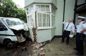 Crashed Vehicle, which left the North Circular Road London and hit a residential house. Pictured are a local authority Building surveyor and traffic policeman - Duncan Phillips - 18-01-2002