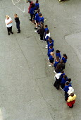 Primary School Children line up in a concrete playground at a North London primary School - Duncan Phillips - 2000s,2002,BAME,BAMEs,black,BME,bmes,boy,boys,child,CHILDHOOD,children,cities,city,class,communicating,communication,concrete,cultural,diversity,duty,EDU education,education,ethnic,ethnicity,female,fe