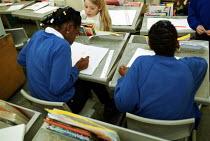 Pupils in a lesson at a C of E primary School, Islington North London - Duncan Phillips - 2000s,2002,adolescence,adolescent,adolescents,art,BAME,BAMEs,black,BME,bmes,child,CHILDHOOD,children,cities,city,class,classroom,CLASSROOMS,comprehensive,COMPREHENSIVES,cultural,desk,desks,diversity,d