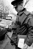 Local Authority Parking Attendant affixing a parking ticket to an illegally parked car. - Duncan Phillips - 2000s,2001,a,attendant,attendants,AUTO,AUTOMOBILE,AUTOMOBILES,AUTOMOTIVE,car,CARS,civil enforcement officer,communicating,communication,COMPUTE,computer,computers,computing,council services,council se