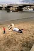 Young man practicing his jumps on a sandy beach beside the river Thames , London - Duncan Phillips - ,2000s,2006,agility,beach,BEACHES,BME Black minority ethnic,cities,city,COAST,coastal,coasts,day out,exercise,exercises,exercising,extreme,Extreme Sports,Free Running,freedom,Freestyle,game,games,Gymn