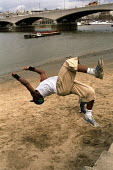 Young man practicing his jumps on a sandy beach beside the river Thames , London - Duncan Phillips - 2000s,2006,agility,beach,BEACHES,BME Black minority ethnic,cities,city,COAST,coastal,coasts,day out,exercise,exercises,exercising,extreme,Extreme Sports,Free Running,freedom,Freestyle,game,games,Gymna