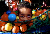Autistic child at an indoor play centre - Duncan Phillips - 1990s,1999,appealing,autism,autistic,BAME,BAMEs,Behavioural,Black,BME,bmes,charming,CHILD,CHILDHOOD,children,cute,difficulties,DIFFICULTY,disabilities,disability,disable,disabled,disablement,disorder,