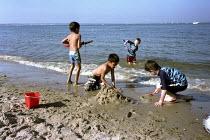 Children building sandcastles on a beach, Dorset - Duncan Phillips - 2000s,2006,beach,BEACHES,Bucket and Spade,building,BUILDINGS,child,CHILDHOOD,Children,COAST,coastal,coasts,cool,EMOTION,EMOTIONAL,EMOTIONS,enjoy,enjoying,enjoyment,EXERCISE,exercises,fun,HAPPINESS,hap