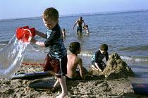 Children building sandcastles on a beach, Dorset - Duncan Phillips - ,2000s,2006,beach,BEACHES,Bucket and Spade,building,BUILDINGS,child,CHILDHOOD,Children,COAST,coastal,coasts,cool,EMOTION,EMOTIONAL,EMOTIONS,enjoy,enjoying,enjoyment,EXERCISE,exercises,fun,HAPPINESS,ha