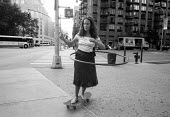 Woman spinning a hulahoop whilst Skateboarding. New York City. USA - Duncan Phillips - .,2000s,2002,cities,City,EXTREME,FEMALE,game games,hula hoop,Leisure,LFL,LIFE,Lifestyle,New York,pavement,pedestrian,pedestrians,people,person,persons,play,playing,recreation,RECREATIONAL,relaxation,r