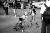 Girl pushing a child in a pushchair, wearing a statue of liberty hat. New York City. USA - Duncan Phillips - 13-08-2002