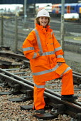 A young woman Network Rail worker in High visibility safety clothes - Duncan Phillips - ,2000s,2004,clothes,depot,DEPOTS,EBF economy,EMOTION,EMOTIONAL,EMOTIONS,employee,employees,Employment,engineer,engineers,FEMALE,happiness,happy,hard hat,hats,high visibility,jacket,job,jobs,LAB LBR Wo