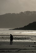 Woman walking alone on a deserted beach in winter - Duncan Phillips - 15-07-2005