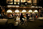 Rickshaws being ridden past Prince Edward Theatre, West End, London - Duncan Phillips - 2010s,2012,cab,cabs,cities,city,hire,holiday,holiday maker,holiday makers,holidaymaker,holidaymakers,holidays,Leisure,LFL,LIFE,london,maker,makers,Night Out,nightlife,PEOPLE,person,persons,RECREATION,