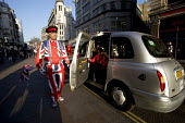 A concierge dressed in Union Jack suit welcoming tourists central London - Duncan Phillips - 2010s,2012,arrival,arrivals,arrive,arrived,arrives,arriving,AUTO,AUTOMOBILE,AUTOMOBILES,AUTOMOTIVE,cab,cabs,car,cars,cas,cities,city,Flag,flags,GB,holiday,holiday maker,holiday makers,holidaymaker,hol