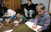 Stressed and tired parents look on as their children draw at home. - Duncan Phillips - 15-07-2005