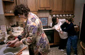 Mother washes the dishes whilst teenage daughters play fight in the kitchen - Duncan Phillips - 15-07-2005