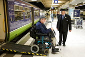 Disabled passenger leaving a train using a ramp, Euston Station, London - Duncan Phillips - 2000s,2005,access,adult,adults,bound,carriage,carriages,cities,city,COMMUTE,commuter,commuters,COMMUTING,disabilities,disability,disable,disabled,disablement,Euston,incapacity,job,jobs,journey,journey