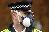 Policeman using face mask for protection from the plume of black smoke from the fire at Buncefield oil depot fire - Duncan Phillips - 2000s,2005,adult,adults,air,Air Quality,apparel,atmosphere,atmospheric,black,breathing,Buncefield,Buncefield oil depot fire,chemical industry,chemicalindustry,CLJ,clothing,depot,DEPOTS,dia accident ac