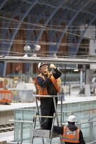Construction workers at St Pancras international Station, London. - Duncan Phillips - 1,2000s,2007,Barlow,BUILDING,BUILDINGS,cities,city,civil,construction,Construction Industry,CTRL,developer,developers,DEVELOPMENT,EBF,EBF Economy,Economic,Economy,electrician,electricians,employee,emp