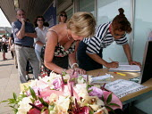 Signing the condolence book at the Two minute silence at Kings Cross station for the victims of terrorist attack, London. - Duncan Phillips - 2000s,2005,7/7,activist,activists,attack,attacking,bomb,bombing,bombings,bombs,CAMPAIGN,campaigner,campaigners,CAMPAIGNING,CAMPAIGNS,commemorative commemoration,communicating,communication,DEMONSTRATI