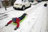 Severe cold weather brings disruption as heavy snow falls in London. Children sledging downhill in the street. - Duncan Phillips - 18-12-2010