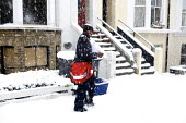 A postal worker delivers the post. Severe cold weather brings disruption as heavy snow falls in London. Postman at work - Duncan Phillips - 2010,2010s,cities,city,CLIMATE,cold,conditions,deliveries,DELIVERING,delivery,disruption,employee,employees,Employment,freezing,frozen,heavy,ice,icy,job,jobs,LAB,LBR,London,low,MAIL,people,post,postal