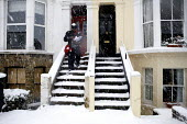 A postal worker delivers the post. Severe cold weather brings disruption as heavy snow falls in London. - Duncan Phillips - 18-12-2010