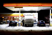 Severe cold weather brings disruption as heavy snow falls in London. Cars filling up at service station. - Duncan Phillips - 2010,2010s,AUTO,AUTOMOBILE,AUTOMOBILES,AUTOMOTIVE,CAR,Cars,cities,city,CLIMATE,cold,conditions,disruption,EBF,Economic,Economy,filling,freezing,frozen,fuel,heavy,highway,ice,icy,London,low,oil,petroch