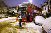 Severe cold weather brings disruption as heavy snow falls in London. Police officers and members of the public try to free standed bus with sand and grit to stop it slipping on the ice. - Duncan Phillips - 18-12-2010
