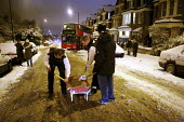 Severe cold weather brings disruption as heavy snow falls in London. Police officers and members of the public try to free standed bus with sand and grit to stop it slipping on the ice. - Duncan Phillips - 2010,2010s,adult,adults,bus,bus service,buses,cities,city,CLIMATE,CLJ,cold,conditions,disruption,force,freezing,frozen,heavy,help,helping,HELPS,highway,ice,icy,London,low,MATURE,metropolitan police se
