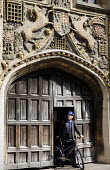 A lecturer emerging from the gate. Doorway to St John's College, Cambridge. Built in 1516 by the mason William Swayne. The statue above the door is of St. John the Evangelist the patron saint of the c... - Duncan Phillips - 2010,2010s,academic,ACADEMICS,ACE,animal,animals,architecture,bicycle,bicycles,BICYCLING,Bicyclist,Bicyclists,bike,bikes,bodies,body,buildings,cambridge,cities,city,college,COLLEGES,culture,cycle,cycl