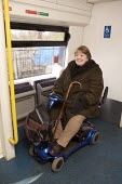 Disabled persons using the railways. - Duncan Phillips - 2000s,2008,Access,cities,city,disabilities,disability,disable,disabled,disablement,embarking,FEMALE,getting,incapacity,journey,journeys,london,minorities,mobility,motorised,motorized,needs,on,onboard,
