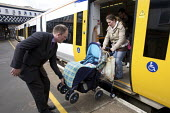Commuter helping family with pushchair. - Duncan Phillips - 2000s,2008,Access,adult,adults,arrival,arrivals,arrive,arrived,arrives,arriving,babies,baby,carriage,carriages,child,CHILDHOOD,children,cities,city,COMMUTE,commuter,commuters,commuting,disembarking,do
